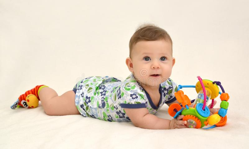 Das nette Baby hält ein Spielzeug auf einem hellen Hintergrund stockfoto