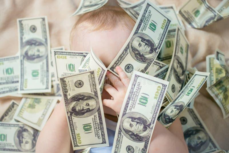 Das nette Baby, das mit dem Geld, geschlossen seinen Augen mit den Händen spielt, um unsichtbar zu sein gewillt ist oder nicht zu lizenzfreie stockfotos