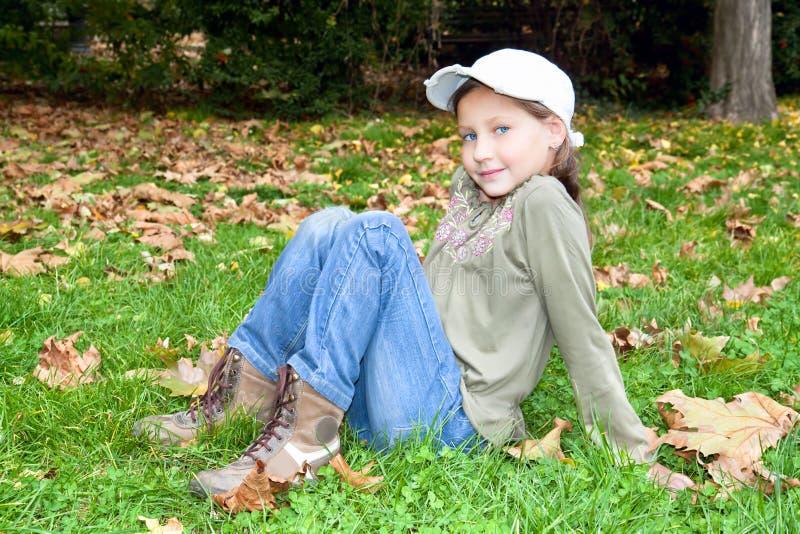 Das nette blauäugige Mädchen, das im Herbst sitzt, färbte Park lizenzfreie stockfotos
