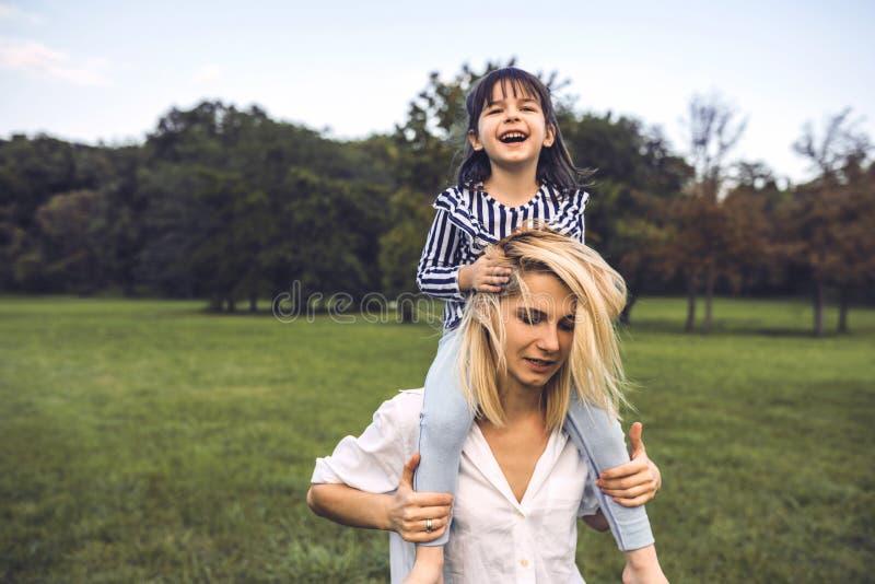 Das nette glückliche kleine Mädchen, das auf den Schultern ihrer schönen Mutter lacht und sitzt, haben den Spaß, der im Park im F lizenzfreie stockfotografie