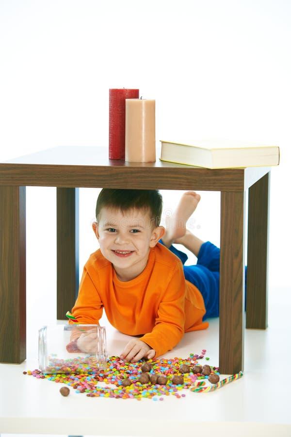 Das nette Kind, das unter Tabelle mit Bonbons liegt, rütteln verschüttet worden stockfotografie