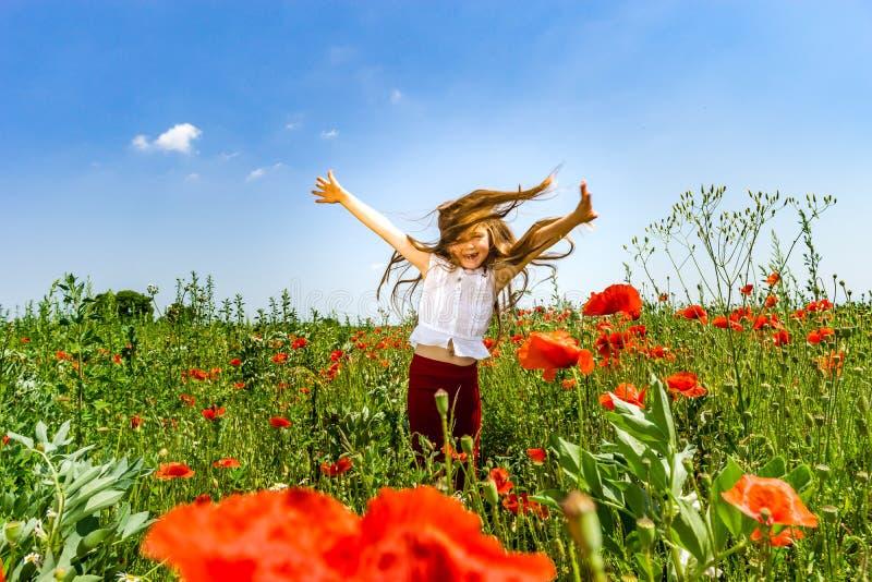Das nette kleine Mädchen, das in den roten Mohnblumen spielt, fangen Sommertag, Schönheit auf stockfoto