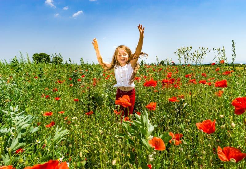 Das nette kleine Mädchen, das in den roten Mohnblumen spielt, fangen Sommertag, Schönheit auf lizenzfreie stockfotos