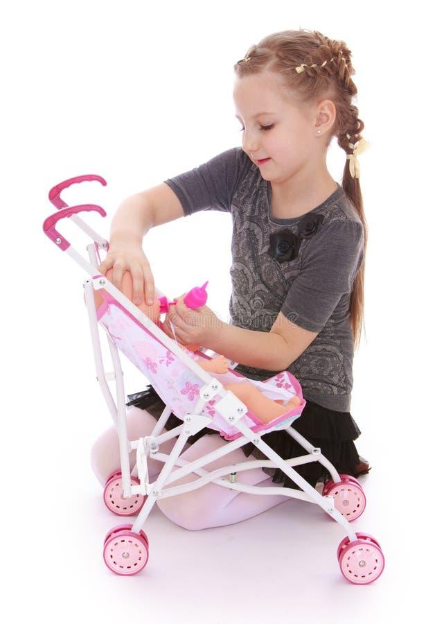 Das nette kleine Mädchen, das mit einer Puppe spielt, setzt sie in den Spaziergänger ein stockbilder