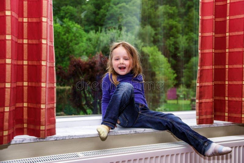 Das nette kleine Mädchen, das mit spielt, drapiert auf dem Fenster stockbilder