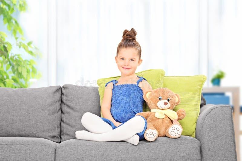 Das nette kleine Mädchen, das mit Teddybären sitzt, betreffen ein Sofa lizenzfreie stockfotografie