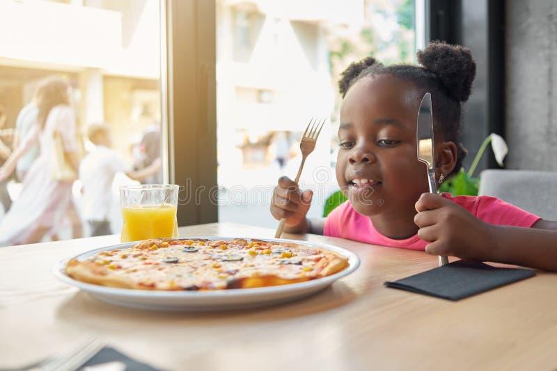 Das nette kleine Mädchen, das geschmackvolle, appetitanregende Pizza betrachtet, kann ` t Wartezeit, zu essen beginnen stockbilder