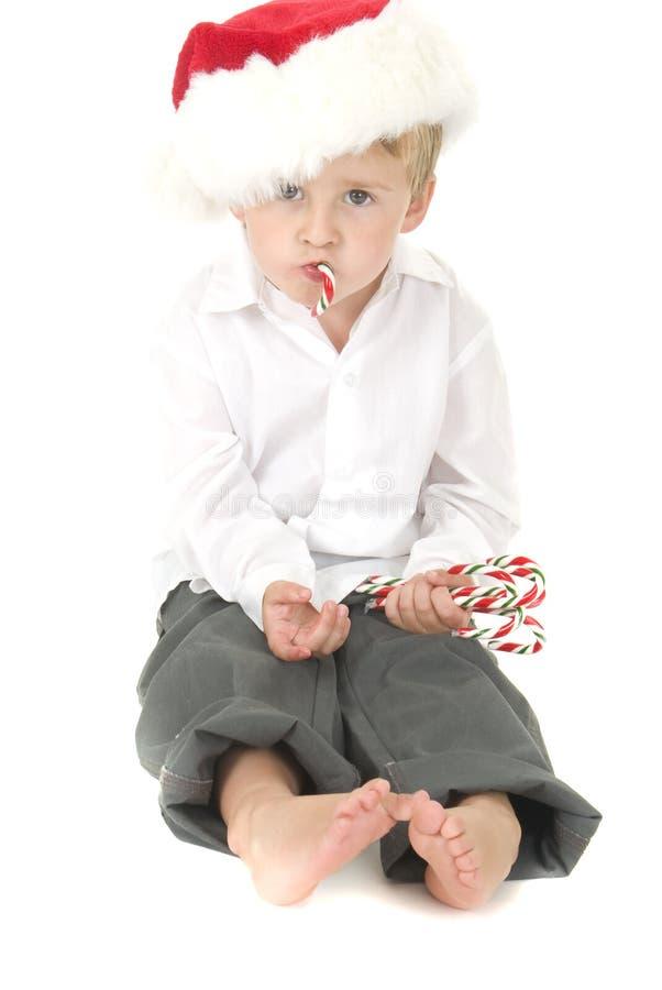 Das nette Kleinkind, das Sankt-Hut trägt, isst Zuckerstange lizenzfreie stockfotos