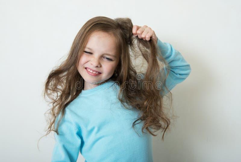 Das nette lächelnde kleine Mädchen, das ihren Haarkamm kämmt, stellt Haar her stockfotografie