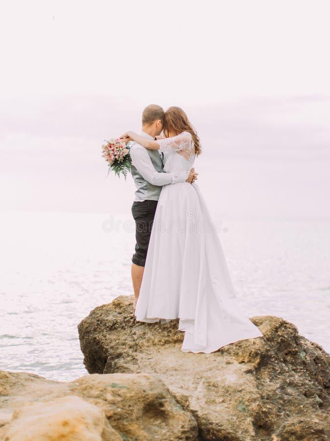 Das nette Porträt der Jungvermählten, die Kopf-an-Kopf- auf der Klippe unter dem Meer umarmen und stehen lizenzfreies stockbild