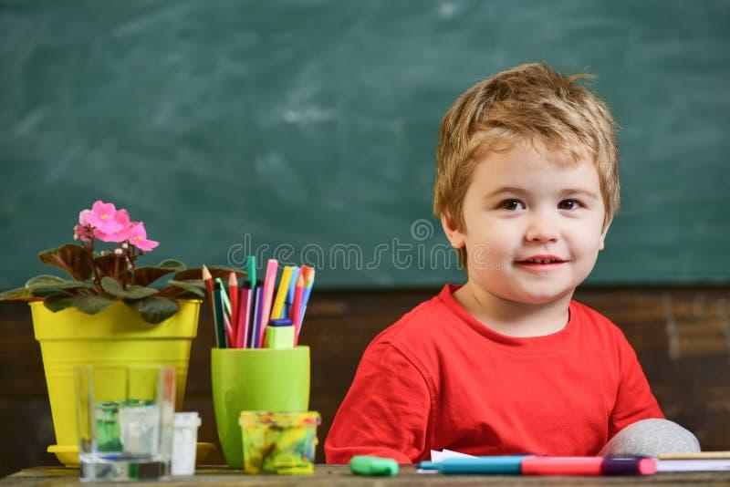 Das nette und nette Kleinkind bereiten vor, um zu studieren Scherzen Sie Jungen im Klassenzimmer nahe Blume im Topf und in den Bl lizenzfreies stockbild