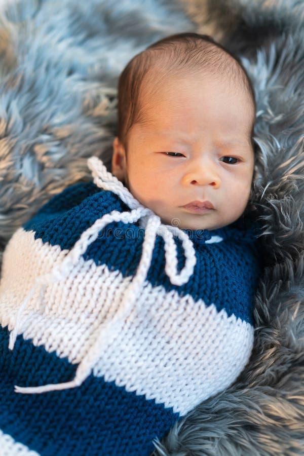 Das neugeborene Baby, das in gewickelt wird, stricken Verpackung auf Pelzbett lizenzfreies stockfoto