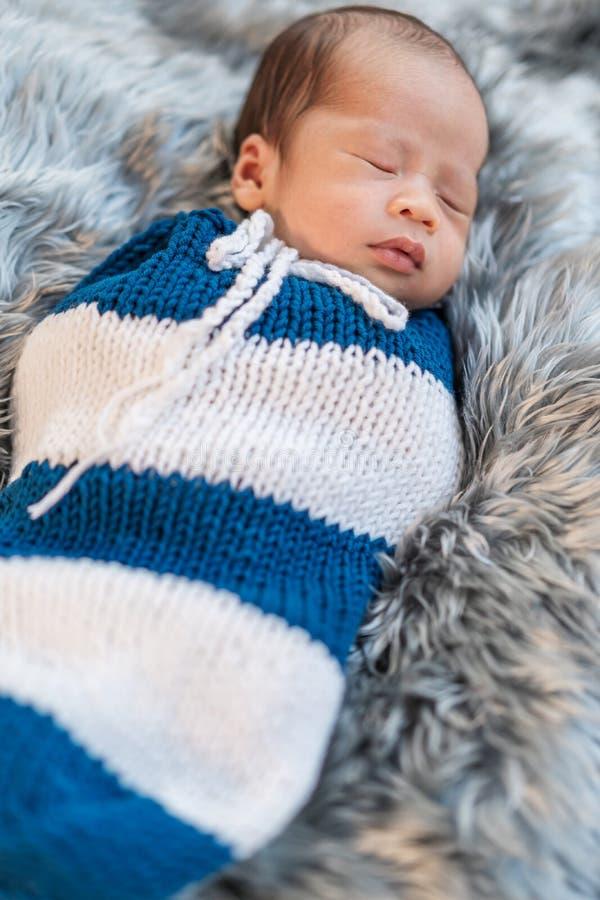 Das neugeborene Baby, das schläft und in wickelt, stricken Verpackung auf Bett stockfotos