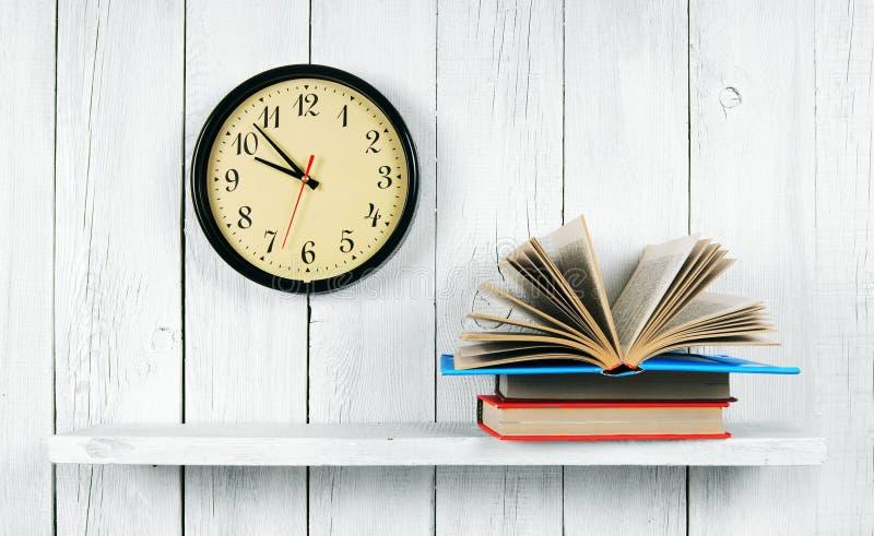 Das offene Buch auf einem hölzernen Regal und Uhren lizenzfreies stockfoto