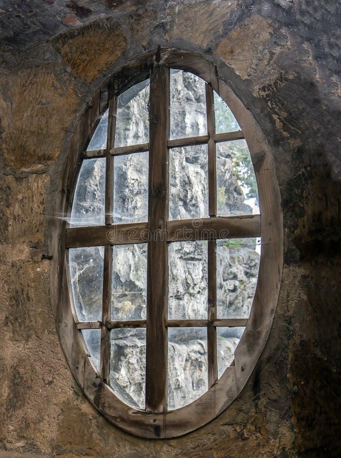 Das ovale Fenster in der Steinwand stockfoto
