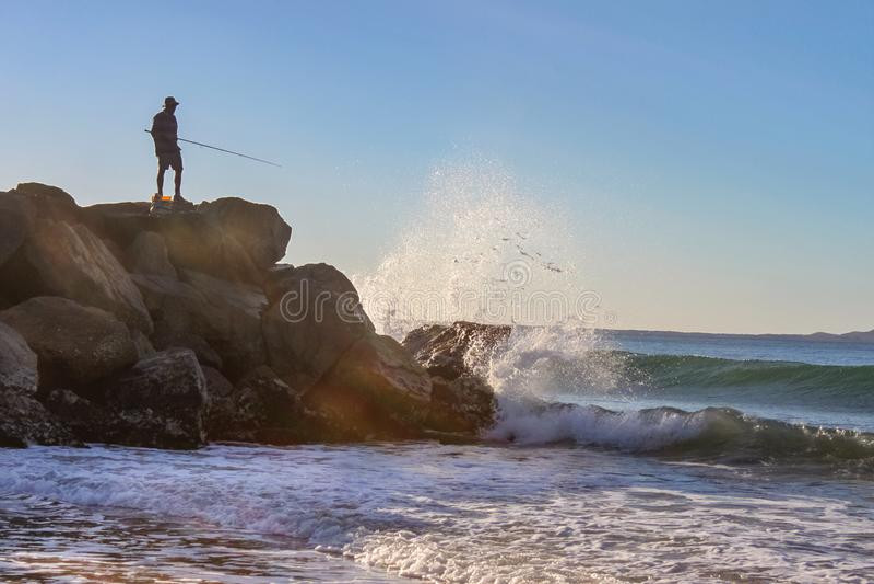 Das Ozeanwasser, das gegen die Felsen spashing ist und up in die Luft, während ein Fischer im sihloutte auf das Zutageliegen sie  lizenzfreies stockbild