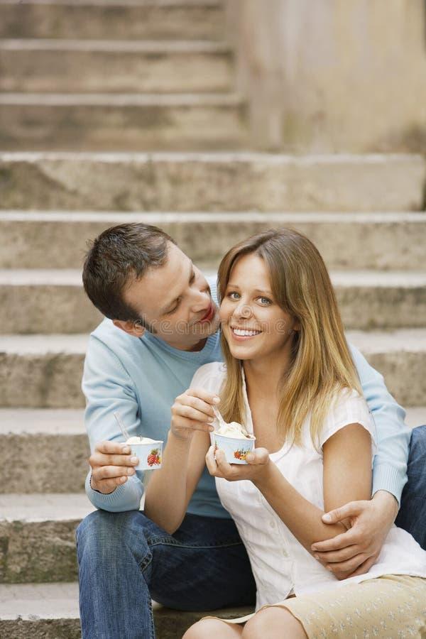 Das Paar, das genießt, Eiscreme auf Schritten lizenzfreie stockfotografie