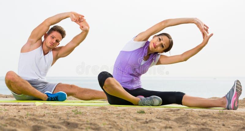 Das Paar, das Yoga tut, wirft das Sitzen auf sonnigem Strand durch Meer auf stockbild