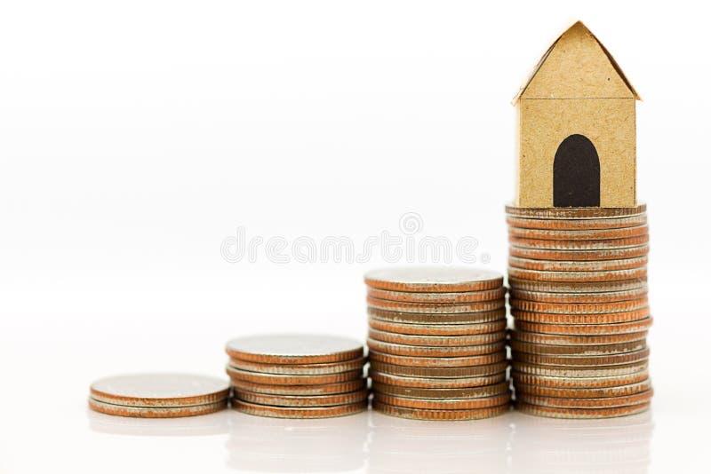 Das Papierhaus auf dem Stapel von Münzen steigt allmählich auf mit, wie finanziell, Kreditvalutakonzept lizenzfreie stockfotos