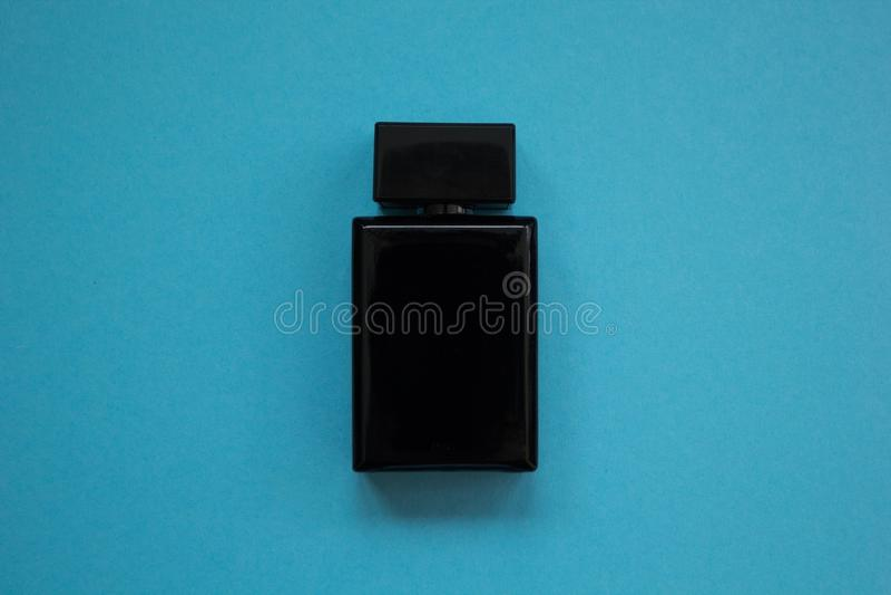 Das Parfüm der Männer in der schönen schwarzen Flasche auf einem blauen Hintergrund stockbild