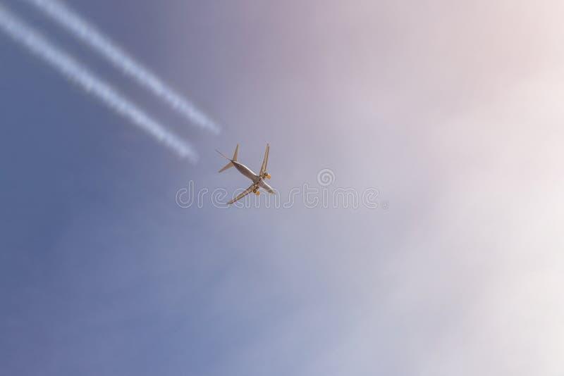 Das Passagierflugzeug, das hoch in den klaren Himmel verlässt Weiß fliegt, schleppt Großes flaches Fliegen während der Sonnenunte lizenzfreies stockbild