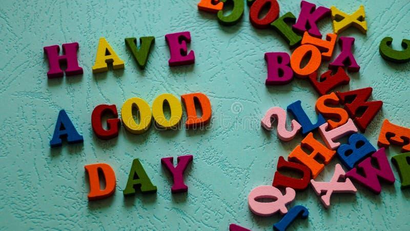 Das Phrase ` haben eine ` des guten Tages hölzerne farbige tadellose Farbe Buchstaben auf dem Tisch stockfotografie