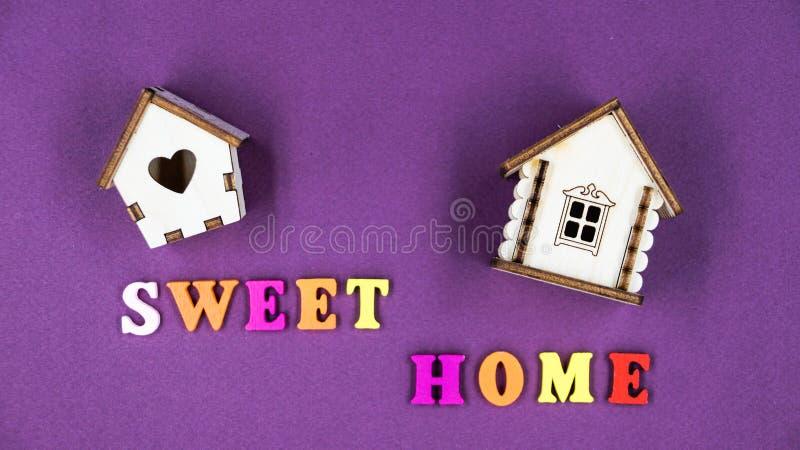 Das Phrase ` süße Haupt-` ausgebreitet auf einem rosa Hintergrund mit zwei Spielzeugholzhäusern stockbild