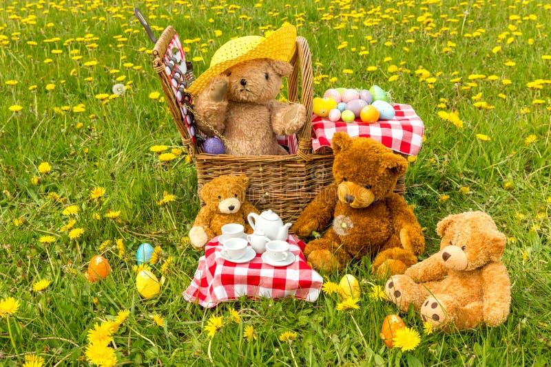 Das Picknick des Teddyb?ren im Sommer mit hellem gelbem L?wenzahn lizenzfreie stockfotografie