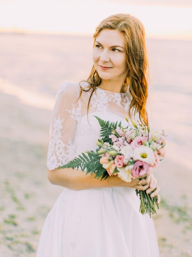 Das Porträt der Braut mit dem Blumenstrauß, der die rechte Seite betrachtet Die Sonnenuntergangzusammensetzung stockbilder