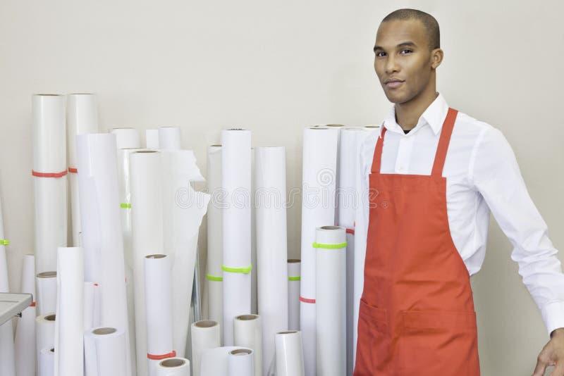 Das Porträt der Druckmaschinearbeitskraft stehend mit Papier rollt im Hintergrund lizenzfreies stockfoto