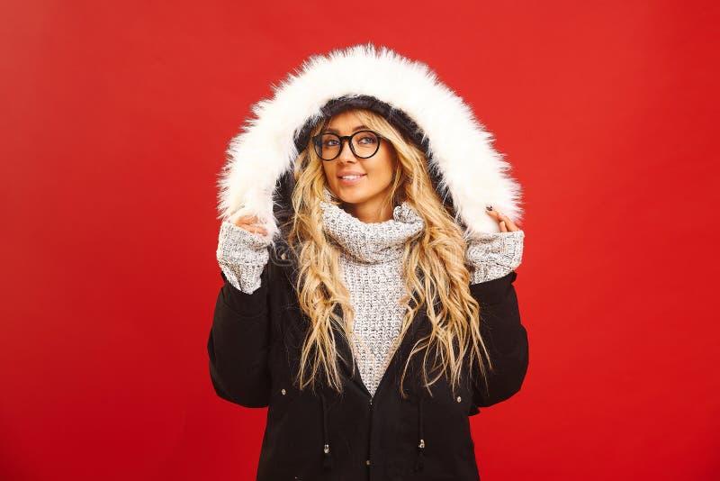 Das Porträt der erfüllten Frau, eine warme Winterjacke mit Haube tragend, hat frohen Ausdruck, fühlt sich warm und bequem lizenzfreies stockfoto