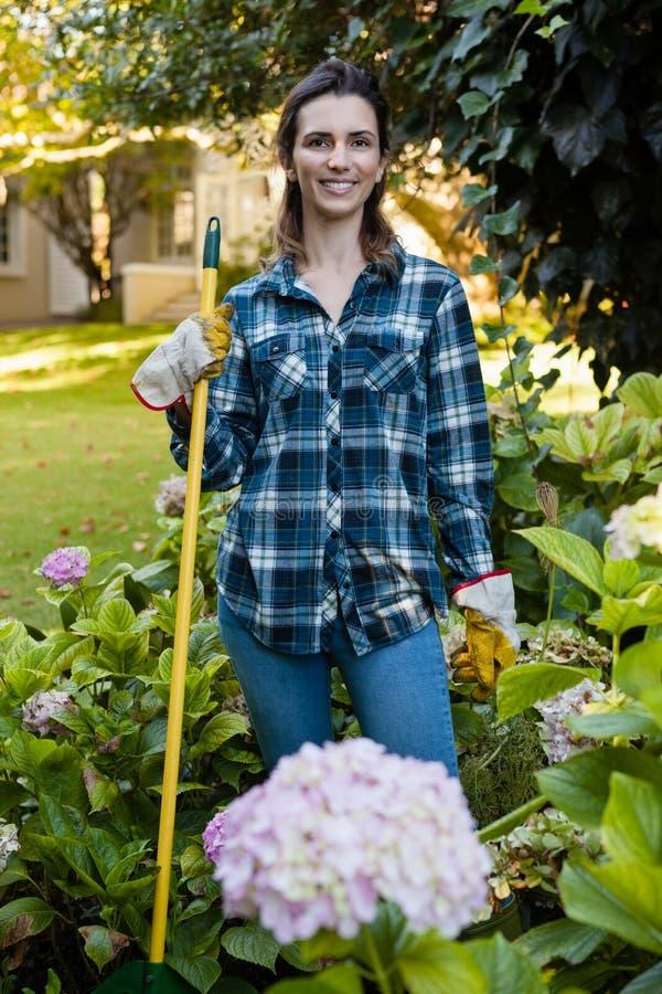 Das Porträt der lächelnden Frau stehend mit Gartenarbeitausrüstung durch Hortensie blüht stockbilder