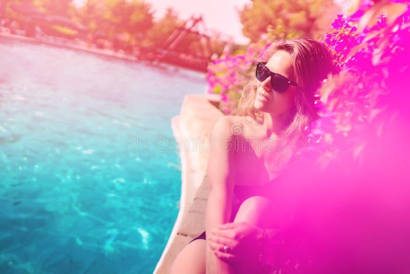 Das Porträt der tragenden Sonnenbrille der Frau durch das Pool, ein nettes erhalten bräunen sich stockfotografie