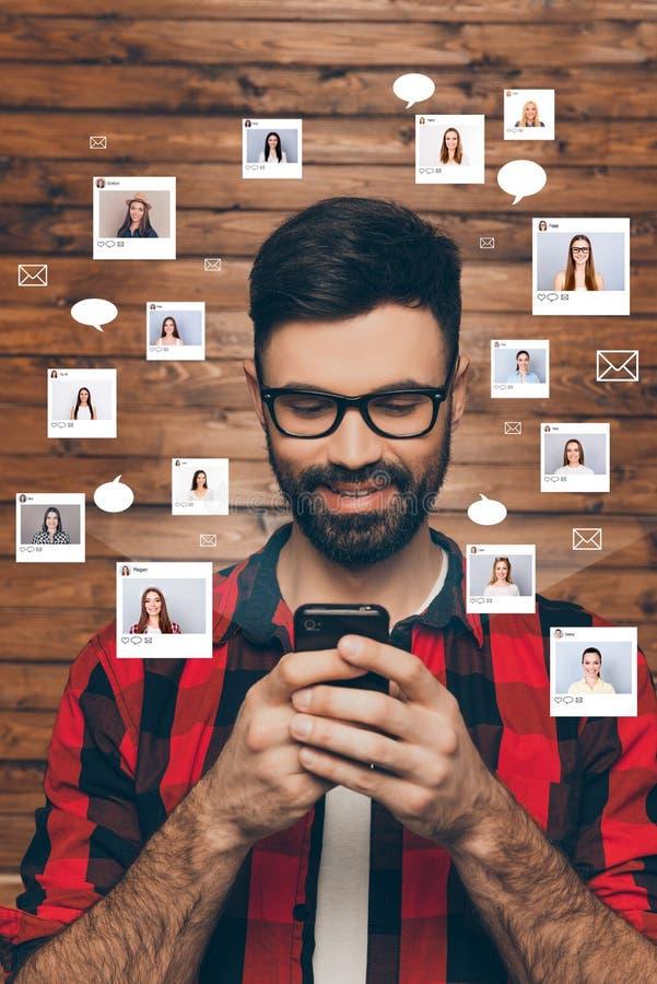 Das Porträt, das lächelnd sitzt er nett ist, er sein junger Kerl, der das intelligente Telefon online gewöhnt wird plaudert, Inte lizenzfreie stockfotos