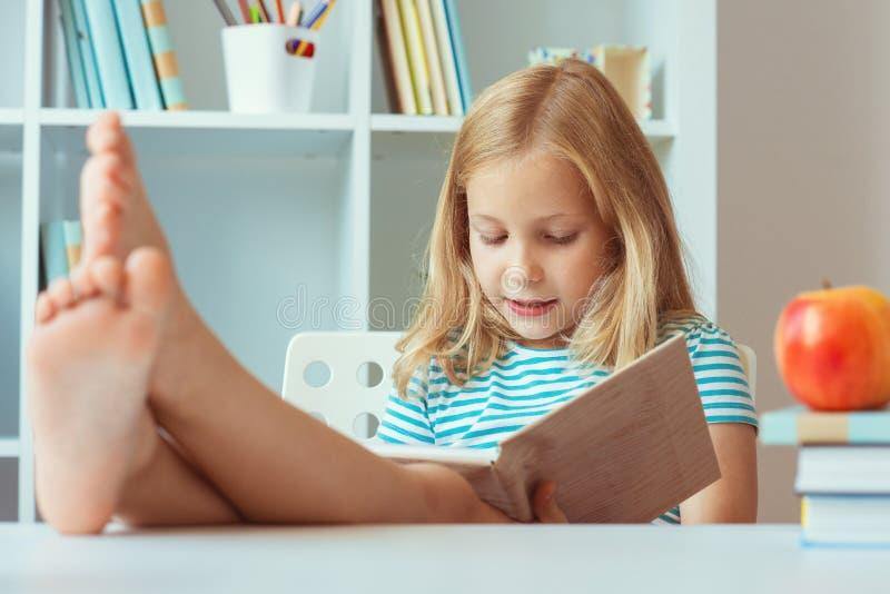 Das Porträt, das wenigen entspannenden Schulmädchens lustig ist, liest Buch am Tisch im Raum zu Hause lizenzfreies stockbild