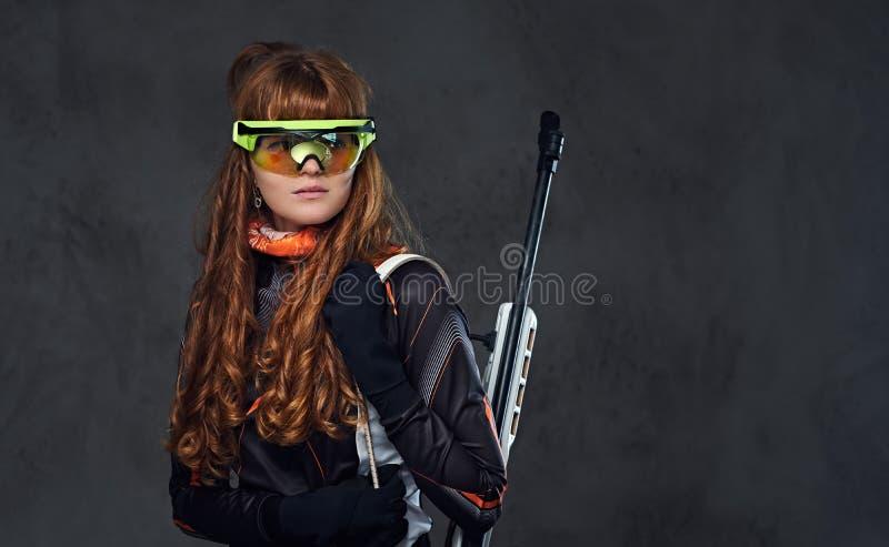 Das posses fêmeas dos desportistas de Biatlon do ruivo arma competitiva imagens de stock royalty free