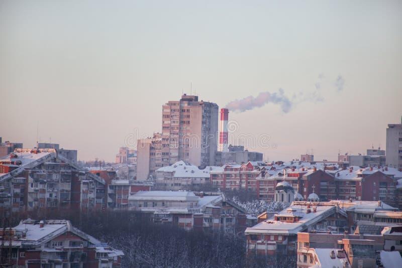 Das Rauchen von den Fabrikschornsteinen der Heizungsanlage strahlt Rauch, Smog bei Sonnenuntergang in der Stadt, Schadstoffe eint stockfotografie