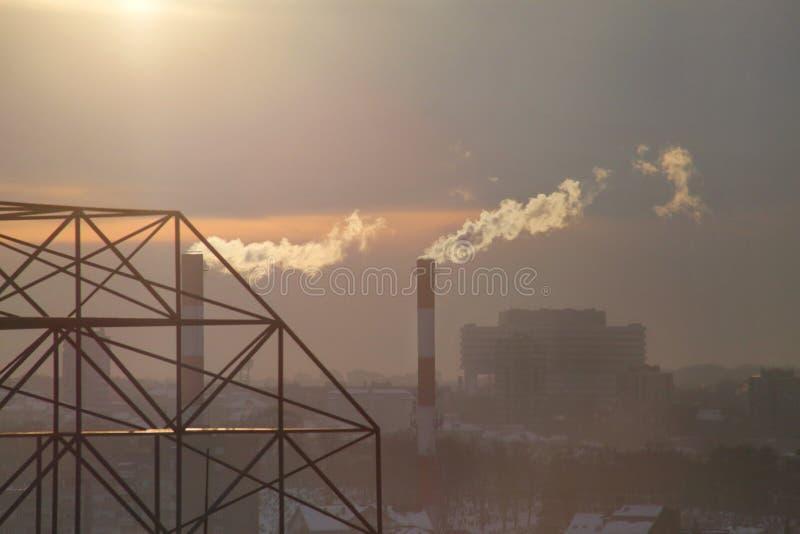 Das Rauchen von den Fabrikschornsteinen der Heizungsanlage strahlt Rauch, Smog bei Sonnenuntergang in der Stadt, Schadstoffe eint lizenzfreies stockbild