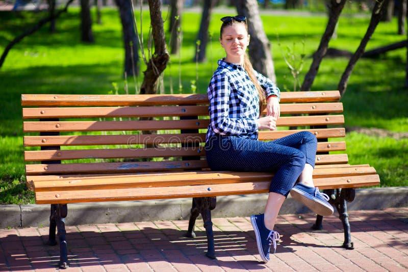 Das reizend Mädchen, das in Park geht und sitzt auf Bank mit geschlossenen Augen lizenzfreies stockbild