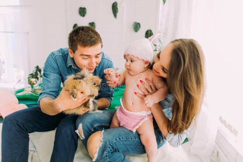Das reizende Familienfoto der Frau, die das Baby und den Mann ihm das Kaninchen im childroom zeigend hält stockfoto