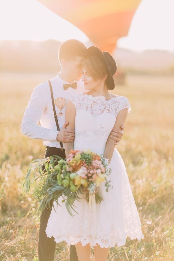 Das reizende vordere Foto der Weinlese kleidete Jungvermählten Der Bräutigam umarmt die Braut mit dem Blumenstrauß zurück in lizenzfreie stockfotografie
