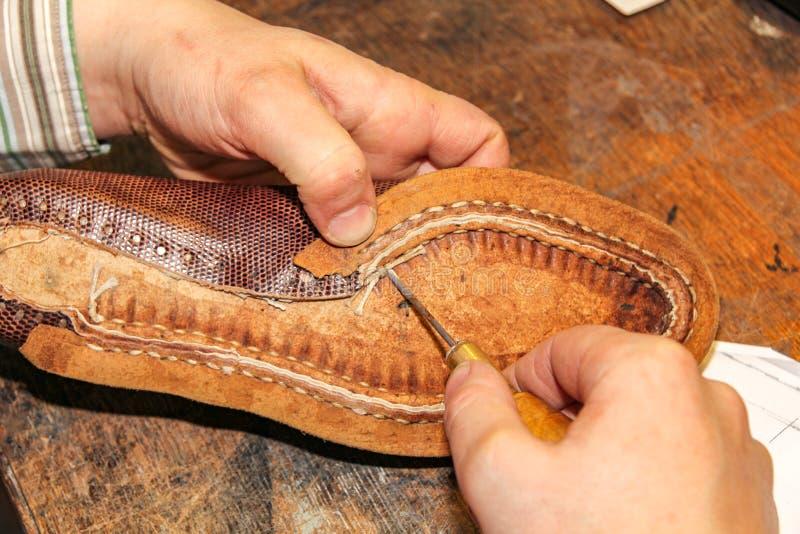 Das Reparieren eines braunen Lederschuhs zeigt die Kunstfertigkeit eines niederländischen Schusters lizenzfreie stockfotografie