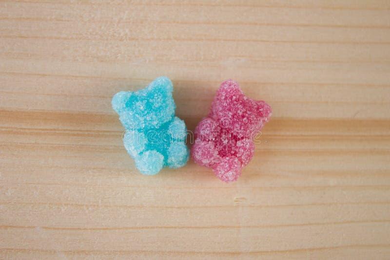 Das Rosa und blaues Gelee gummiartig sind, betreffen h?lzernen Hintergrund stockfoto