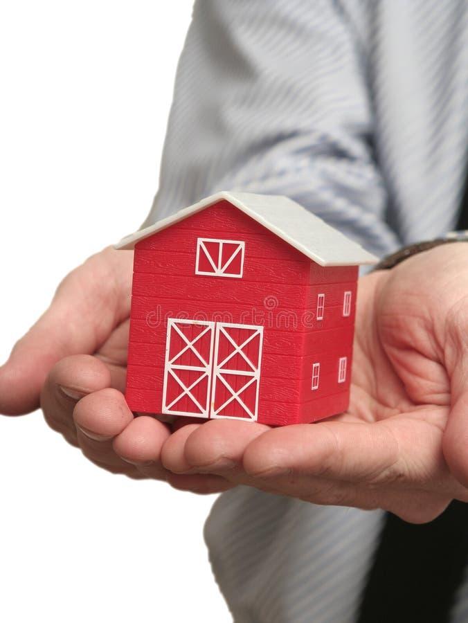 das rote Haus in einer Hand stockbild