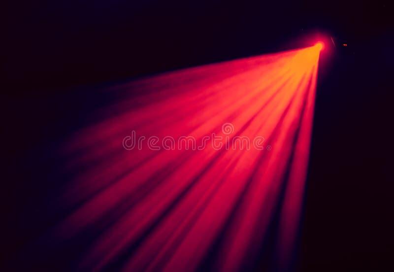 Das rote Licht von den Scheinwerfern durch den Rauch am Theater während der Leistung lizenzfreie stockfotos