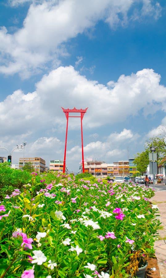 Das rote riesige Schwingen ist eine religiöse Struktur in Phra Nakhon mit buntem Blumengarten am Tag des bewölkten Himmels lizenzfreies stockbild