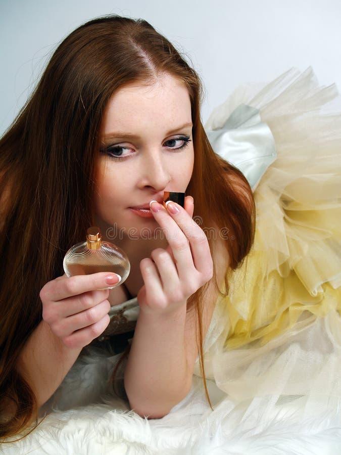 Das rote schöne Mädchen inhaliert ein Duftstoffaroma lizenzfreie stockfotos