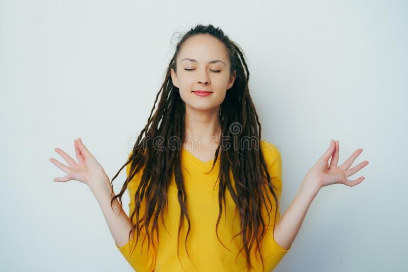Das ruhige gesunde schöne Mädchen mit Dreadlocks und in einer gelben hellen Strickjacke meditierend für Entspannung mit Augen sch stockbild