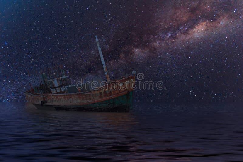 Das ruinierte Schiff unter sternenklarer Nacht mit offenbar Milchstraße stockfoto