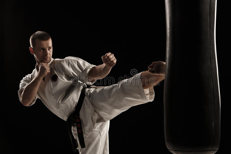 Das runde Karate treten herein einen Sandsack stockfoto